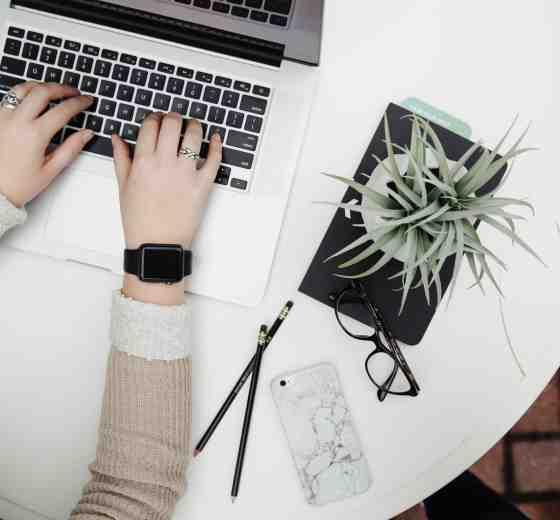 Una persona en una mesa utilizando una computadora portátil.