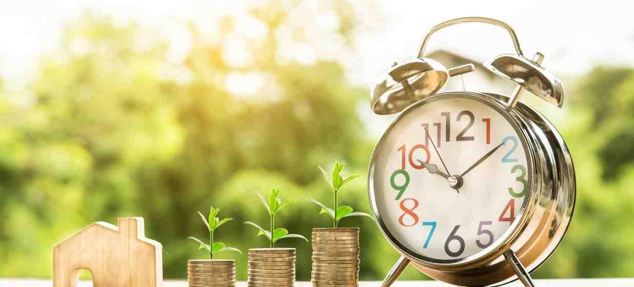 filas de monedas a la par de un reloj